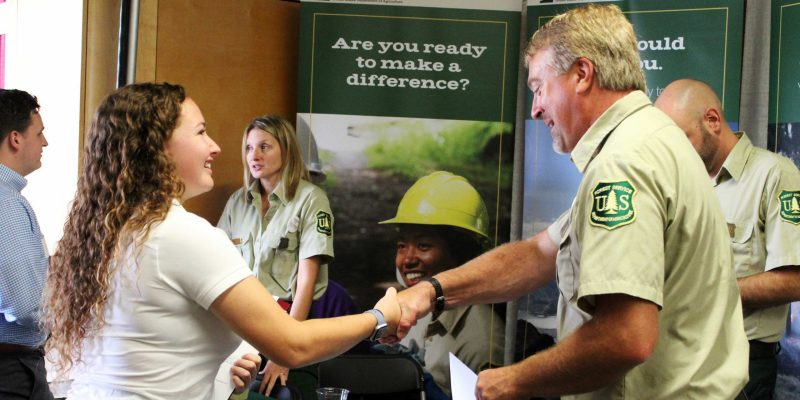 A young woman shakes hands across a table with a man wearing a green U.S. Forest Service uniform. Several other people are visible in the background.