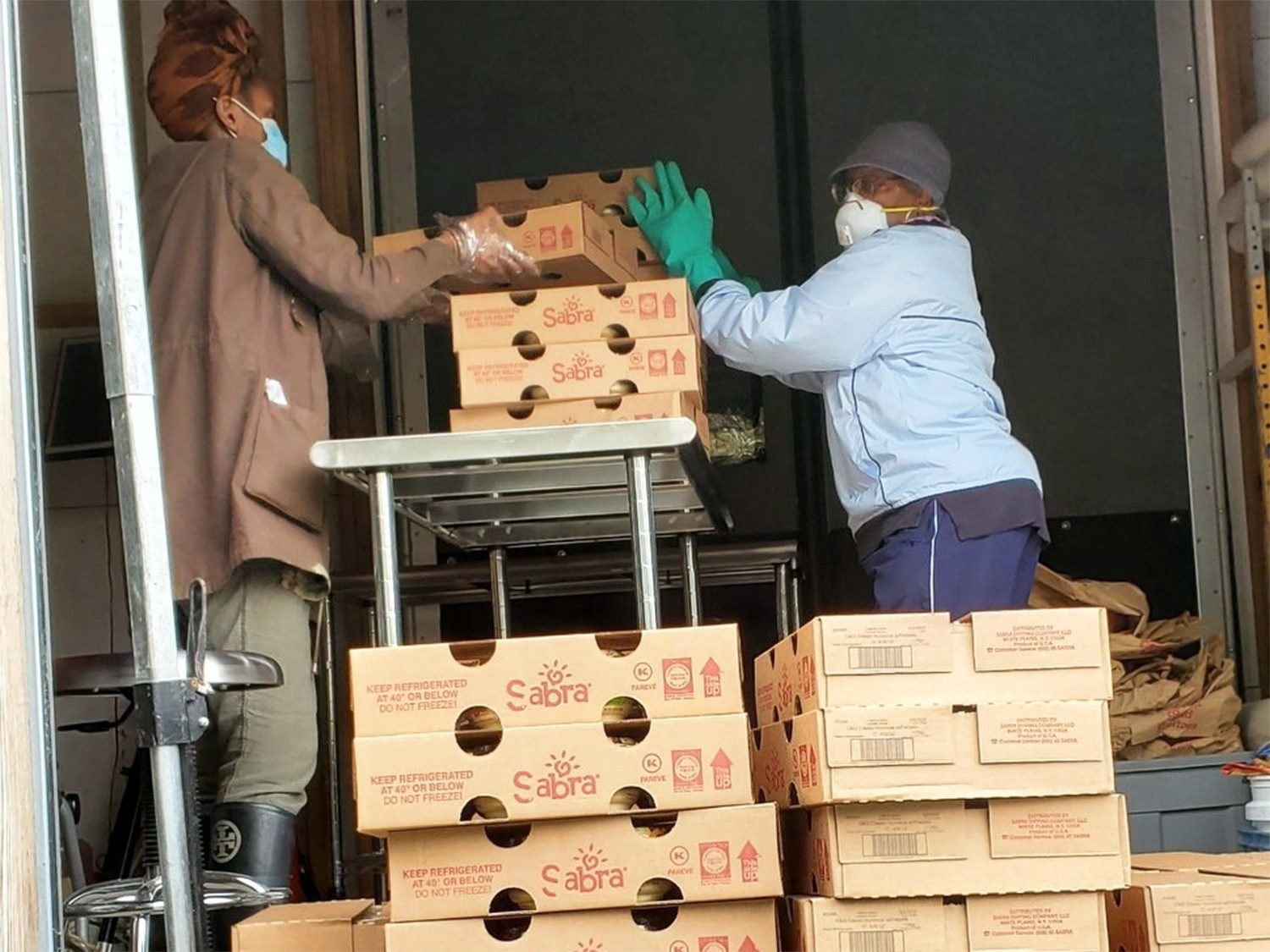 Morgan Maxwell and Cynthia Martinunload hummus and pretzel snacks at the Harding Street Agricultural Center