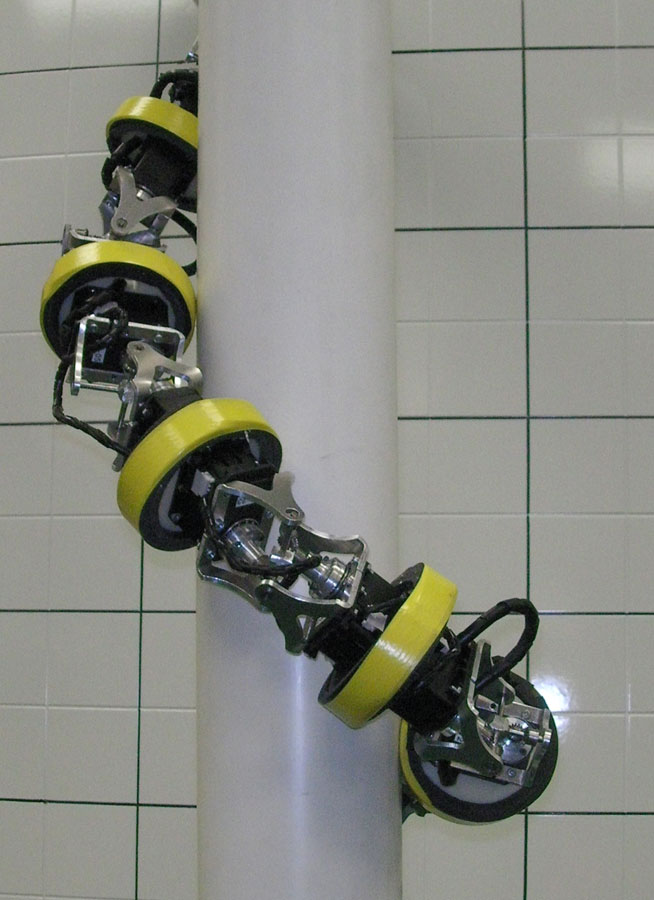 This HyDRAS serpentine robot prototype climbs a pole by converting the oscillating motion of the joints to a whole body rolling motion to climb up pole-like structures.