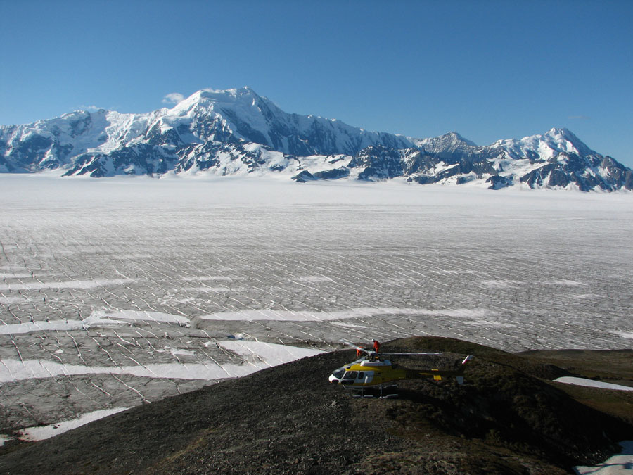 The Bagley ice field is believed to cover a large fault (Bagley fault), discovered by the STEEP project, which is thought to have become highly active in response to accelerated glacial erosion in the last million years. Resulting from differential rock motion across this structure, the large mountain in the background is moving up relative to the hill beneath the helicopter at about 10,000 feet per million years. Photo courtesy of Aaron L. Berger.