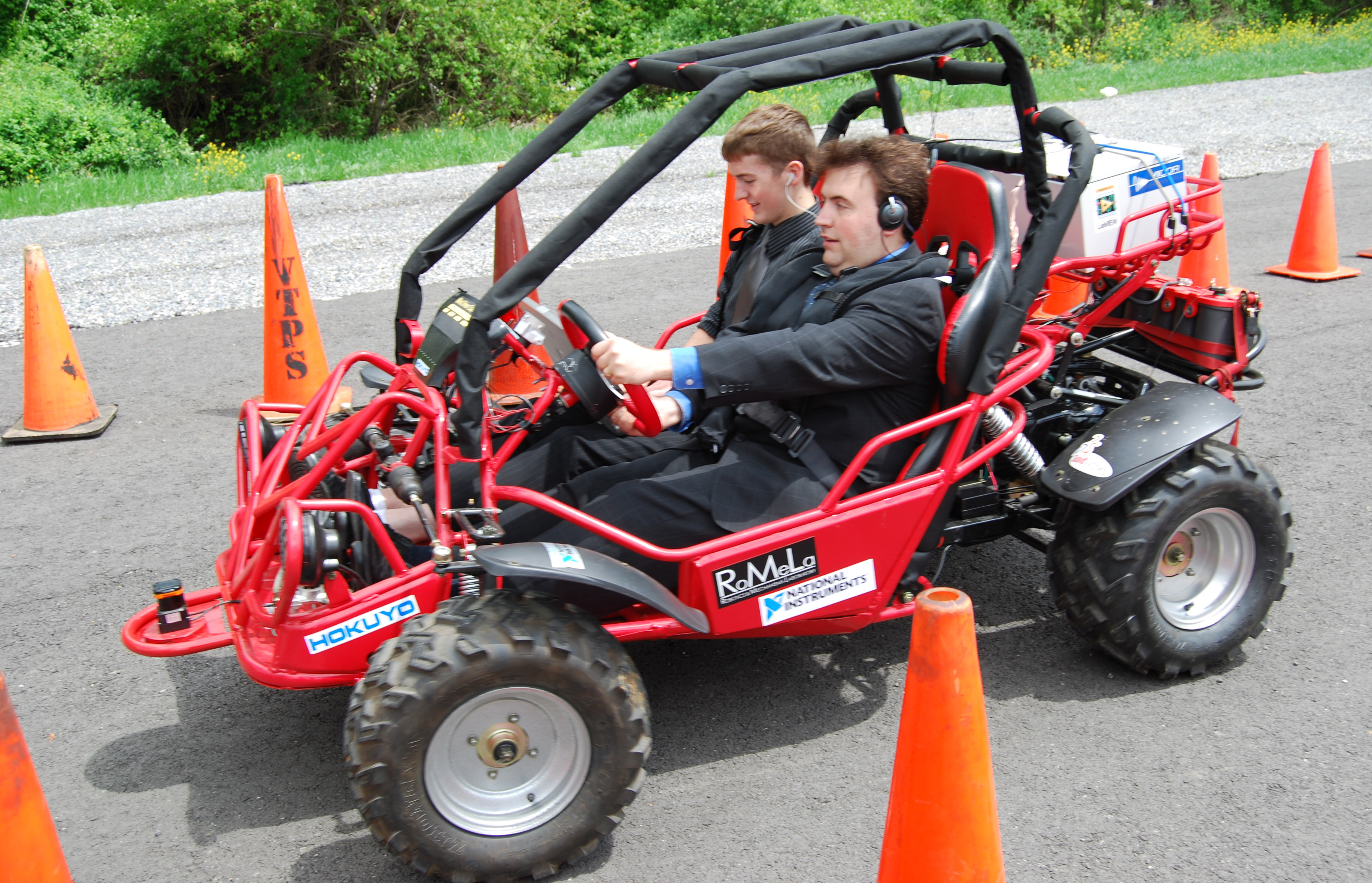 Mark Riccobono, executive director of the National Federation of the Blind's Jernigan Institute, drives the Virginia Tech Blind Driver Challenge vehicle through an obstacle course of traffic cones on a campus parking lot. In the passenger seat is Greg Jannaman, who led the student team within the mechanical engineering department during the past year, and is monitoring the software of the vehicle..
