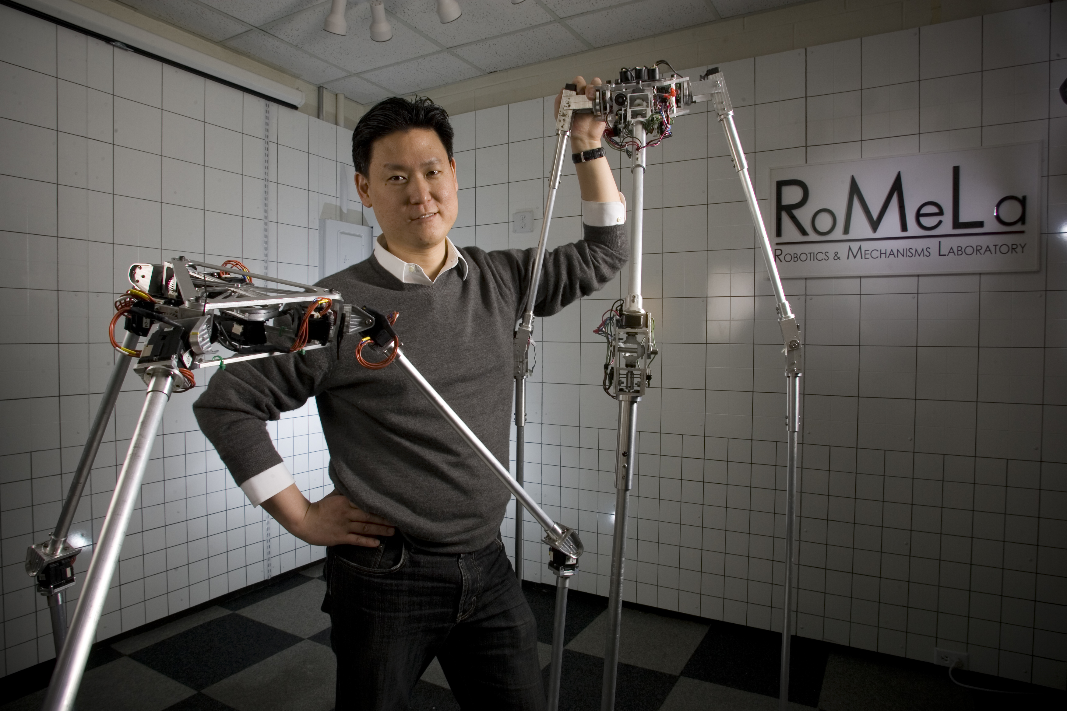 Dennis Hong stands with one of his robot creations, STriDER.