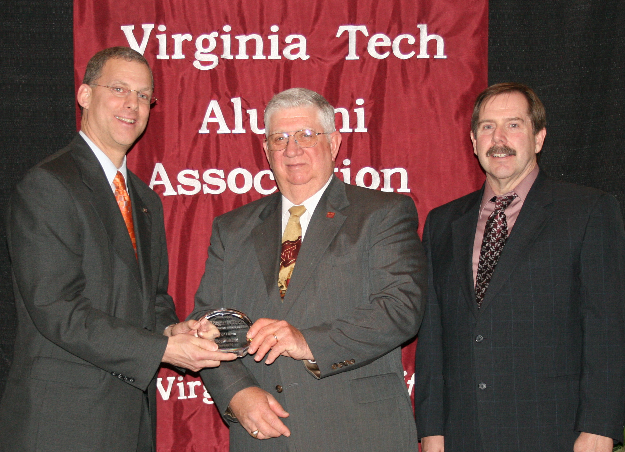 Bruce Holland (center) receives the Hall of Fame Award from Alan Grant (left), dean of the College of Agriculture and Life Sciences, and Kevin Boyle (right), professor and head of the Department of Agricultural and Applied Economics, at the annual Alumni Awards Program on March 5, 2010.