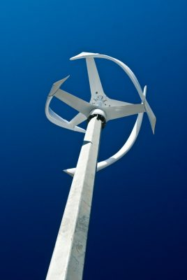 Dramatic photo of a white verticle wind turbine against a blue sky