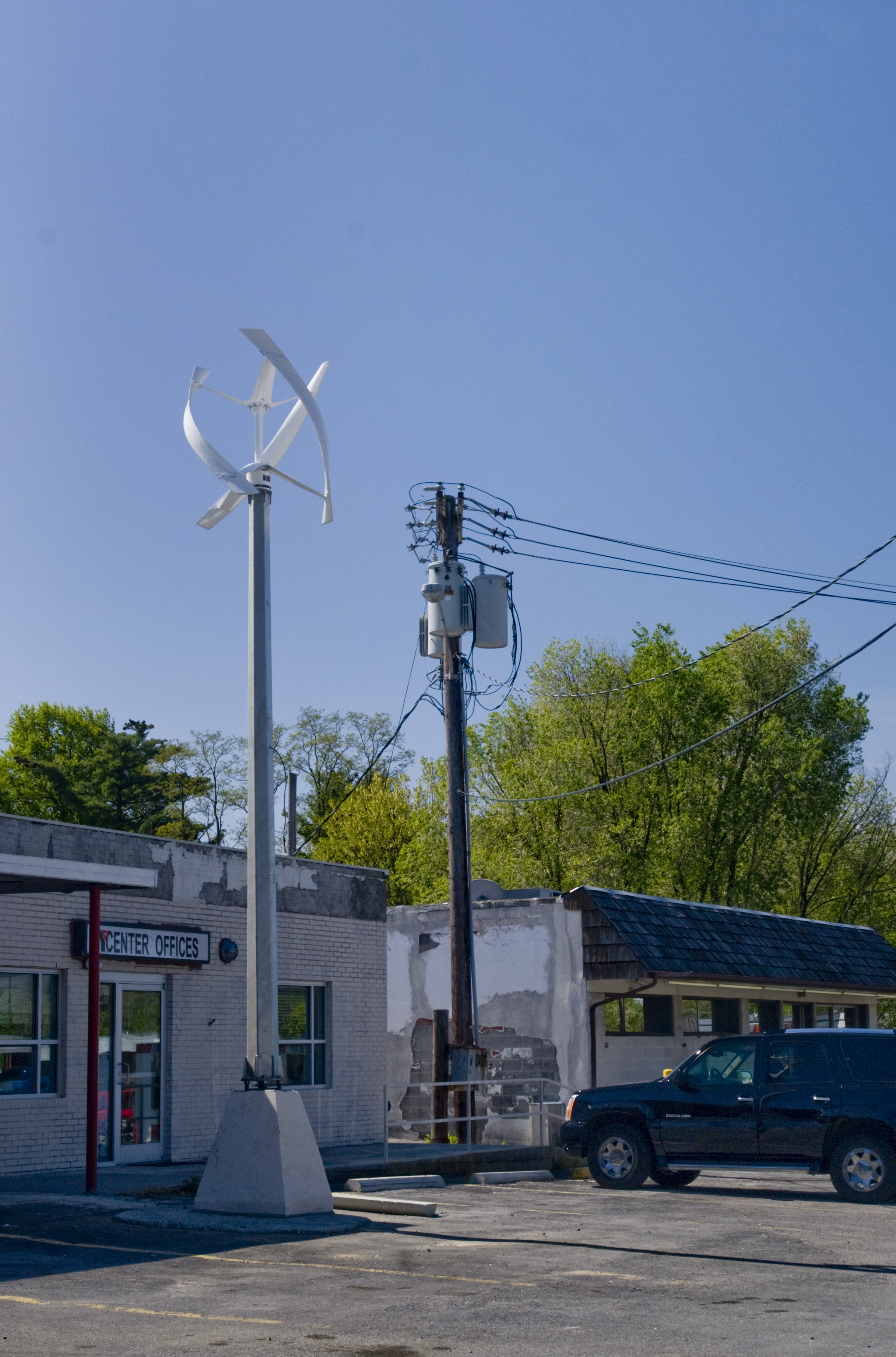 A verticle wind turbine in the forground with an electric pole in the near background