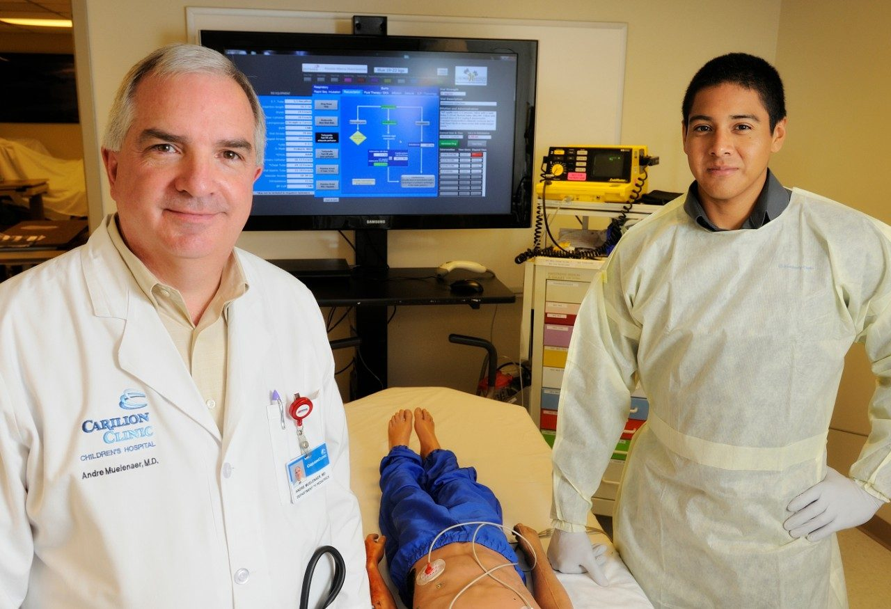 At a practice emergency room facility, Dr. Andre A. Muelenaer Jr. (left) and Virginia Tech College of Engineering graduate student Carlos Guevara display the large-screen digital format of the Broselow Tape, developed in conjunction with the college, Carilion Clinic Children's Hospital and the tape's original creator, James Broselow.