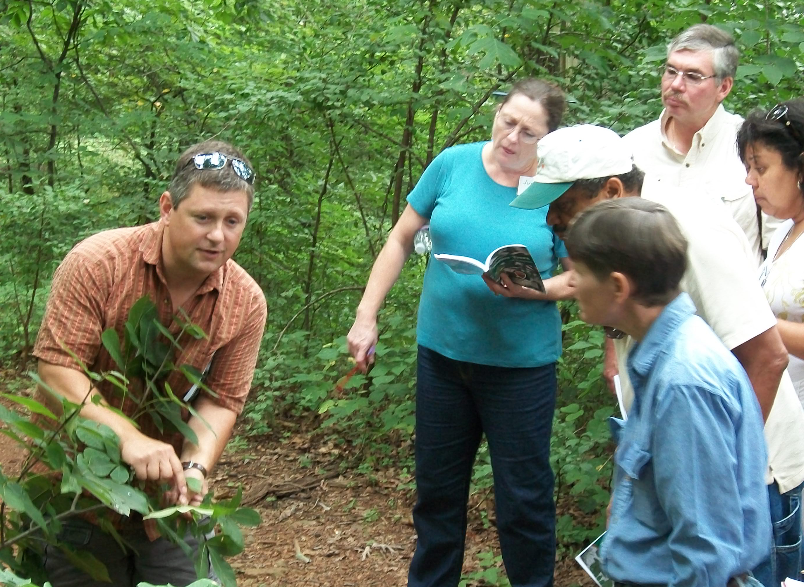 In a forest setting, John Peterson points to leaves on a bush while students look on.