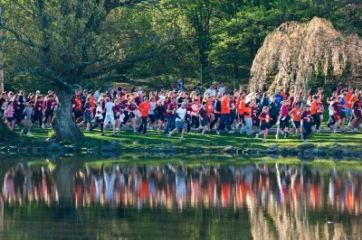 A large group of runners run past the Duckpond