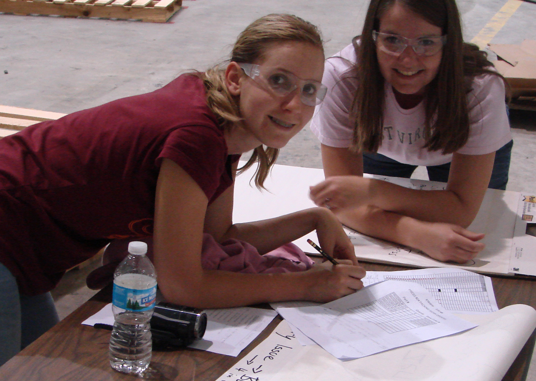 Two women wearing safety goggles write on papers covering a table on the Swan Corporation plant floor.