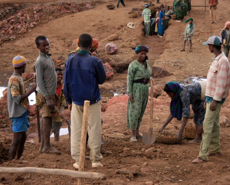 A group of Ethiopians work build a stream crossing.