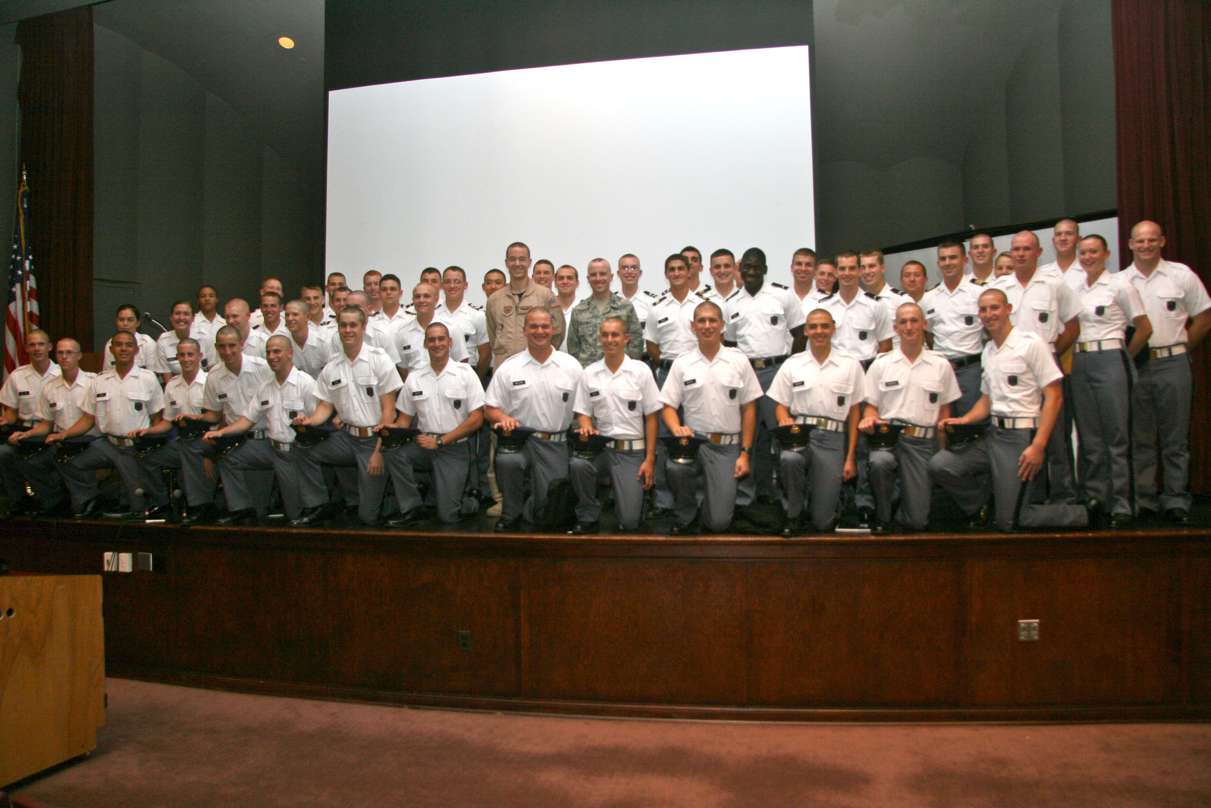Capt. Dan Richardson (center, left), U.S. Air Force and Capt. Chris Callaway (center, right), U.S. Air Force, previous Gunfighter panelists standing on stage with members of their former cadet company. Echo Company