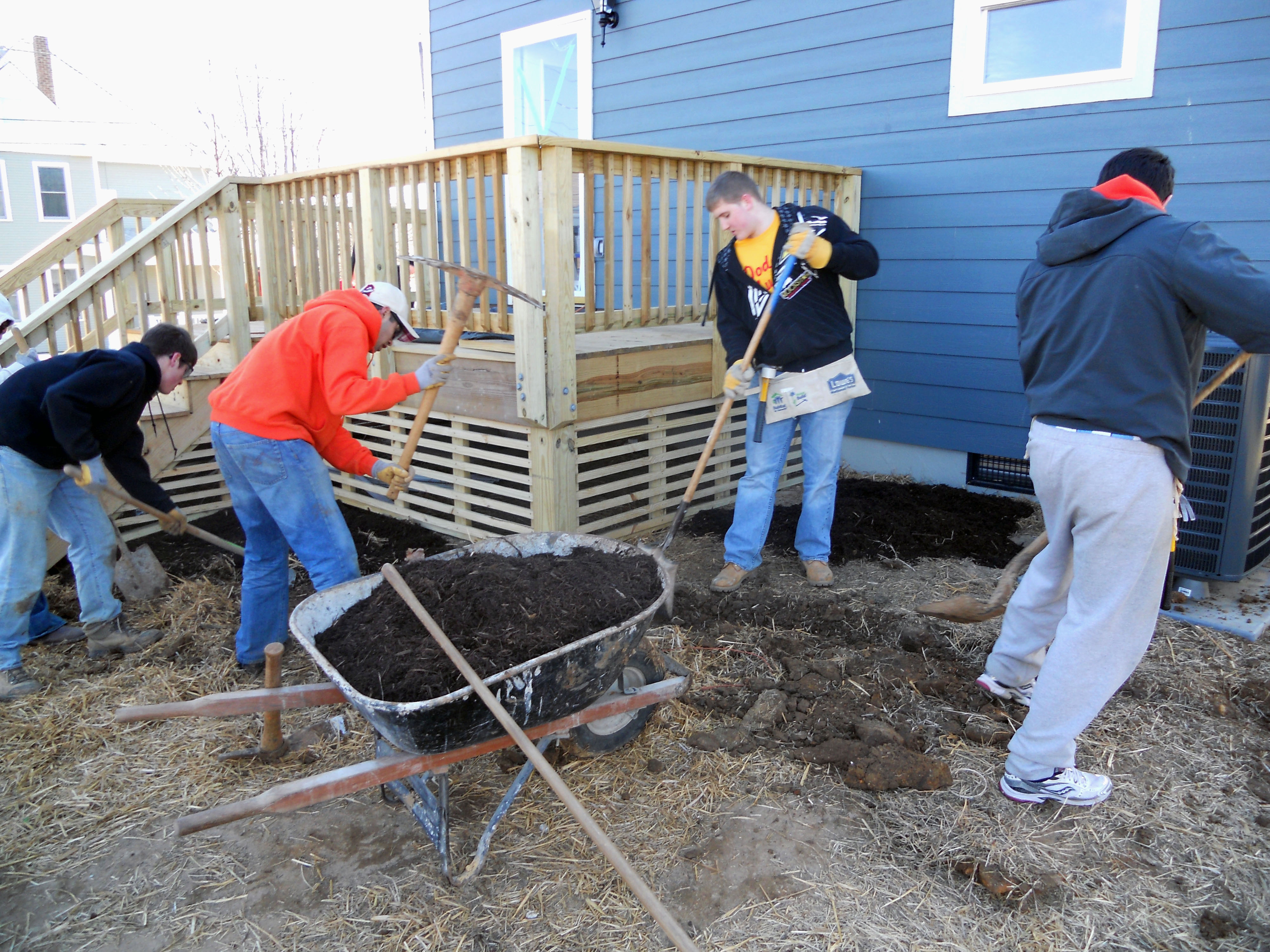 Students landscaping in the garden of a Habitat for Humanity house