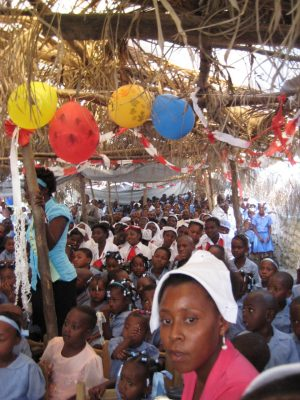 Villagers gather to celebrate with balloons and song during March as the bridge is dedicated in Ti Péligre, Haiti.