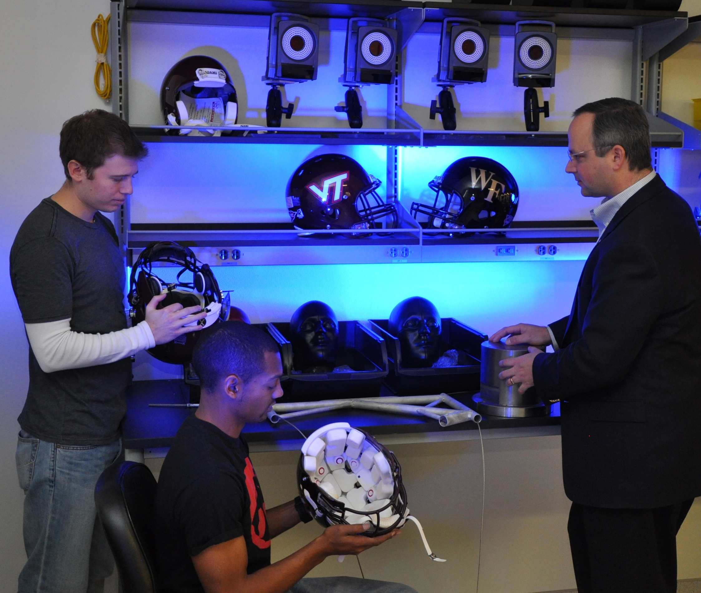 Two professors and a student examine football helmets.