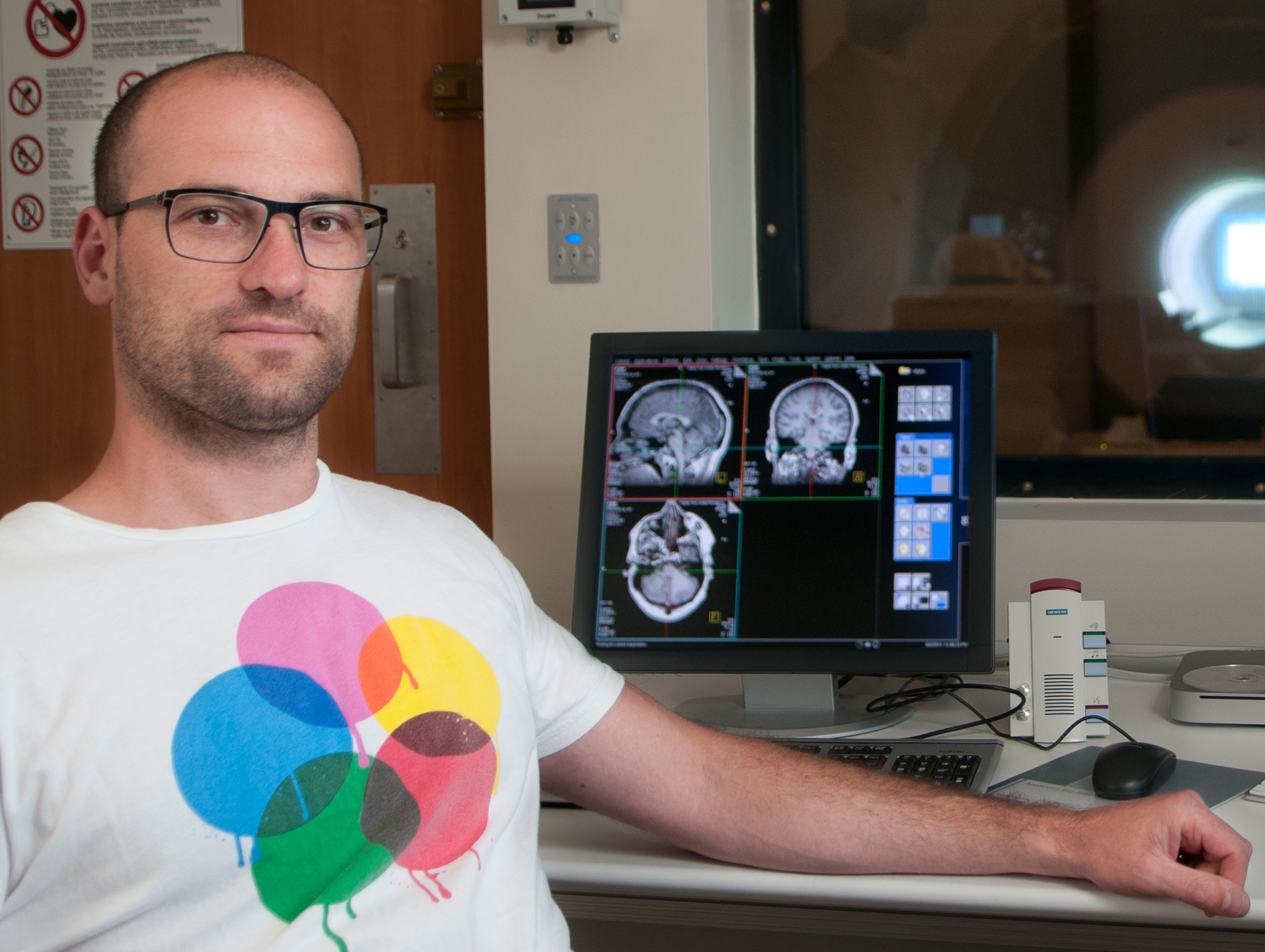Ulrick Kirk in front of monitor showing brain scans