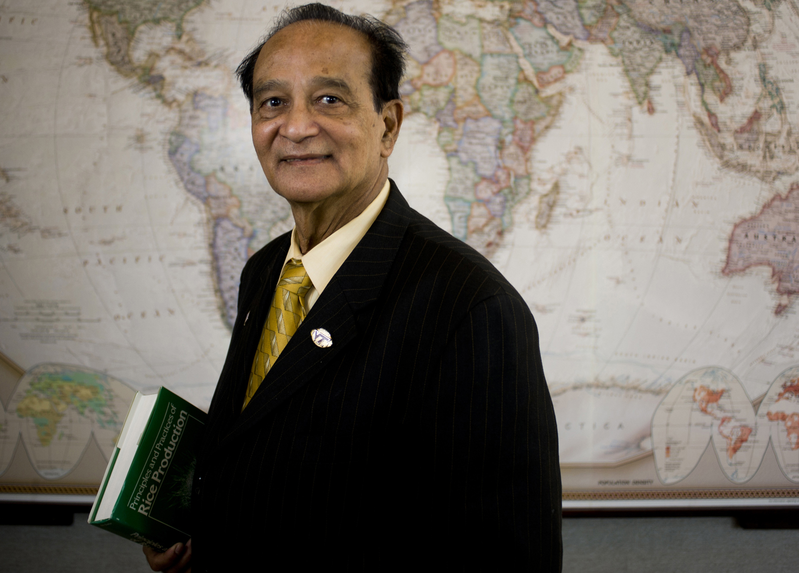 S.K. De Datta standing in front of world map