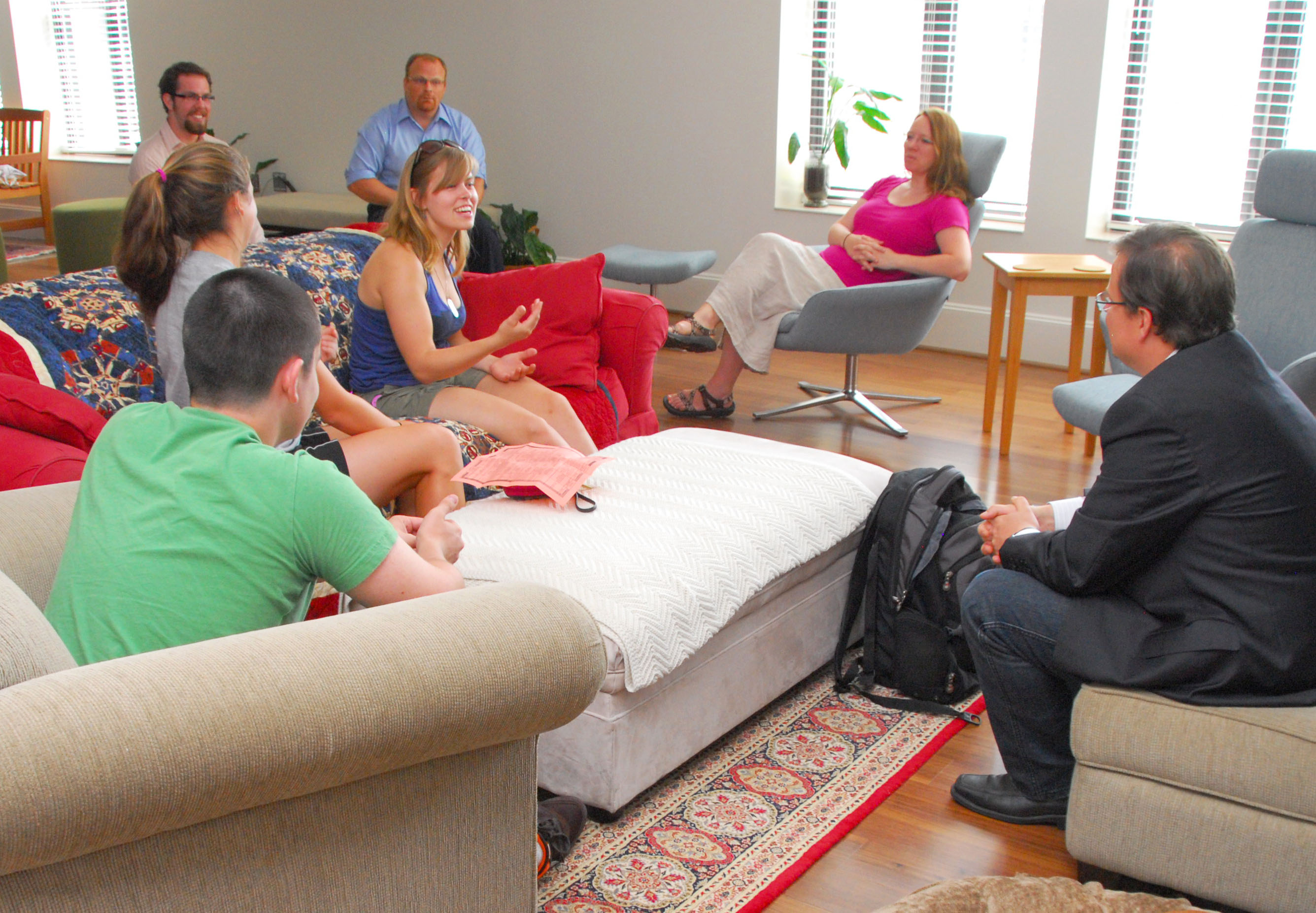 Students, faculty, and faculty principals talk in the sitting room at the Honors Residential College.