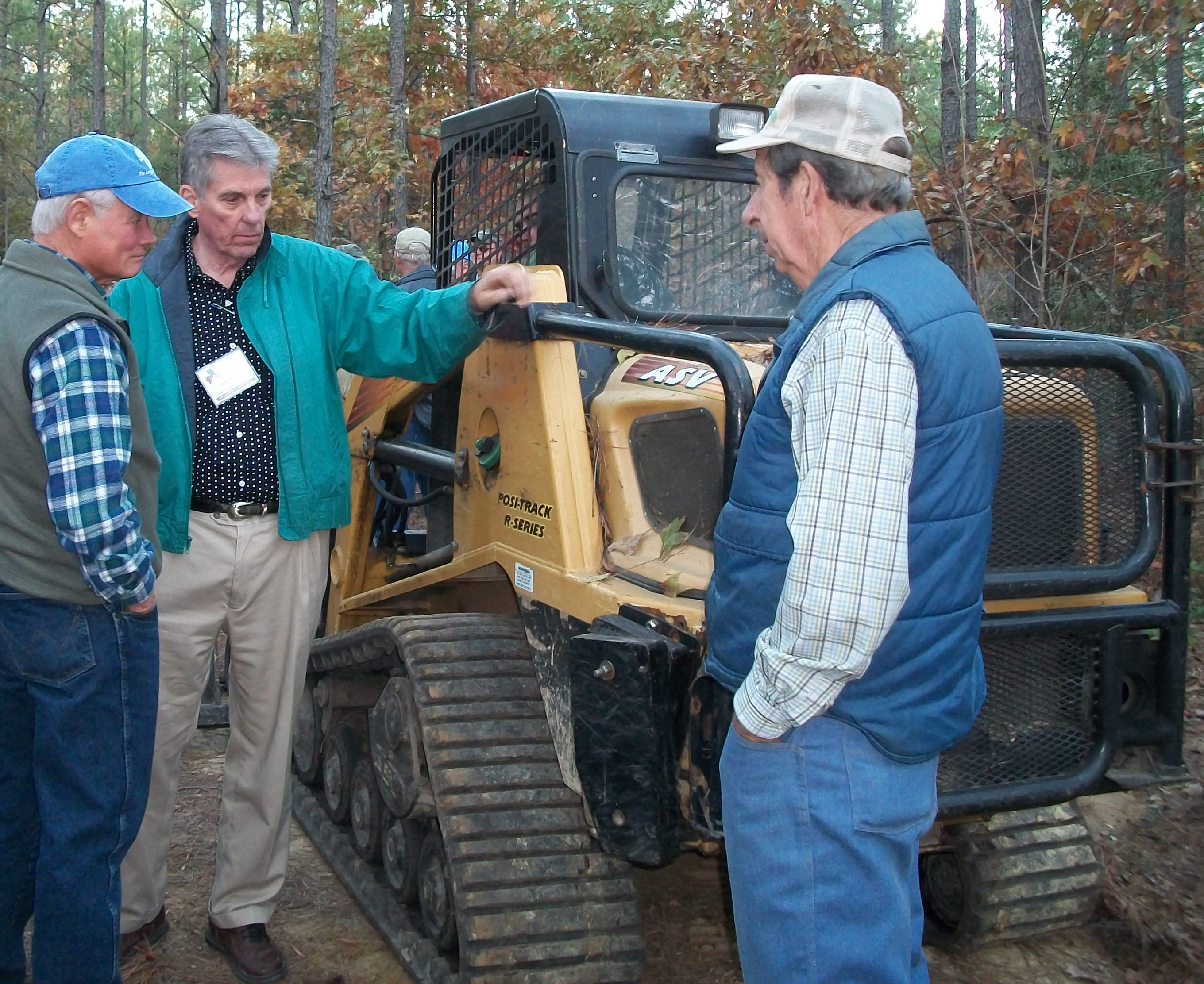 Three men stand looking at a small-scale skidder in a forest.
