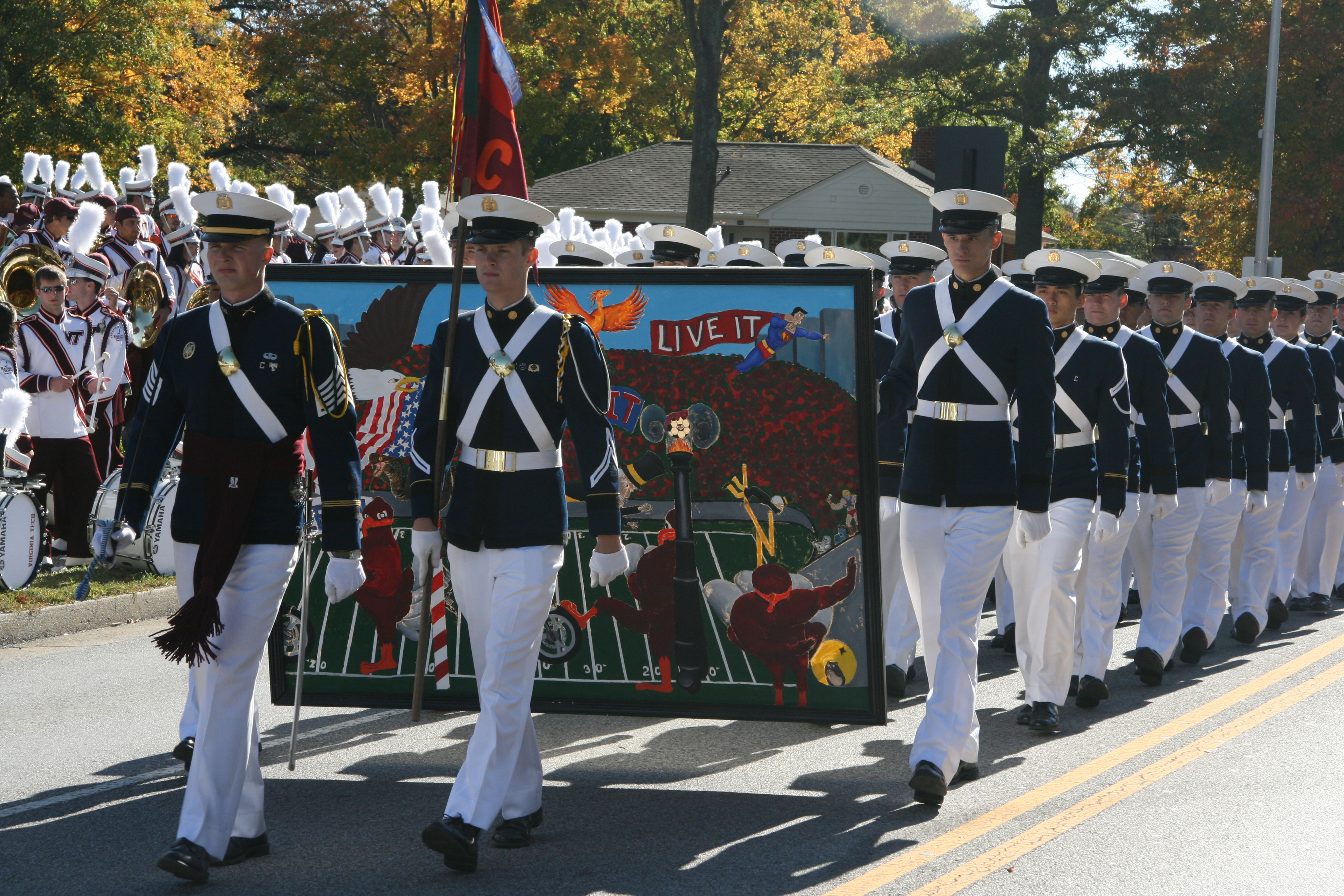 Members of the Virginia Tech Corps of Cadets march during the 2010 Homecoming Parade carrying their unit homecoming banner