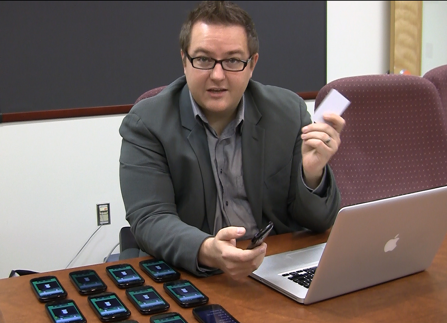 Jules White with laptop that controls the bank of cell phones