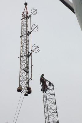 A worker is perched atop the lower section of a radio tower waiting to guide the upper section into place that is being lowered from above by a crane.