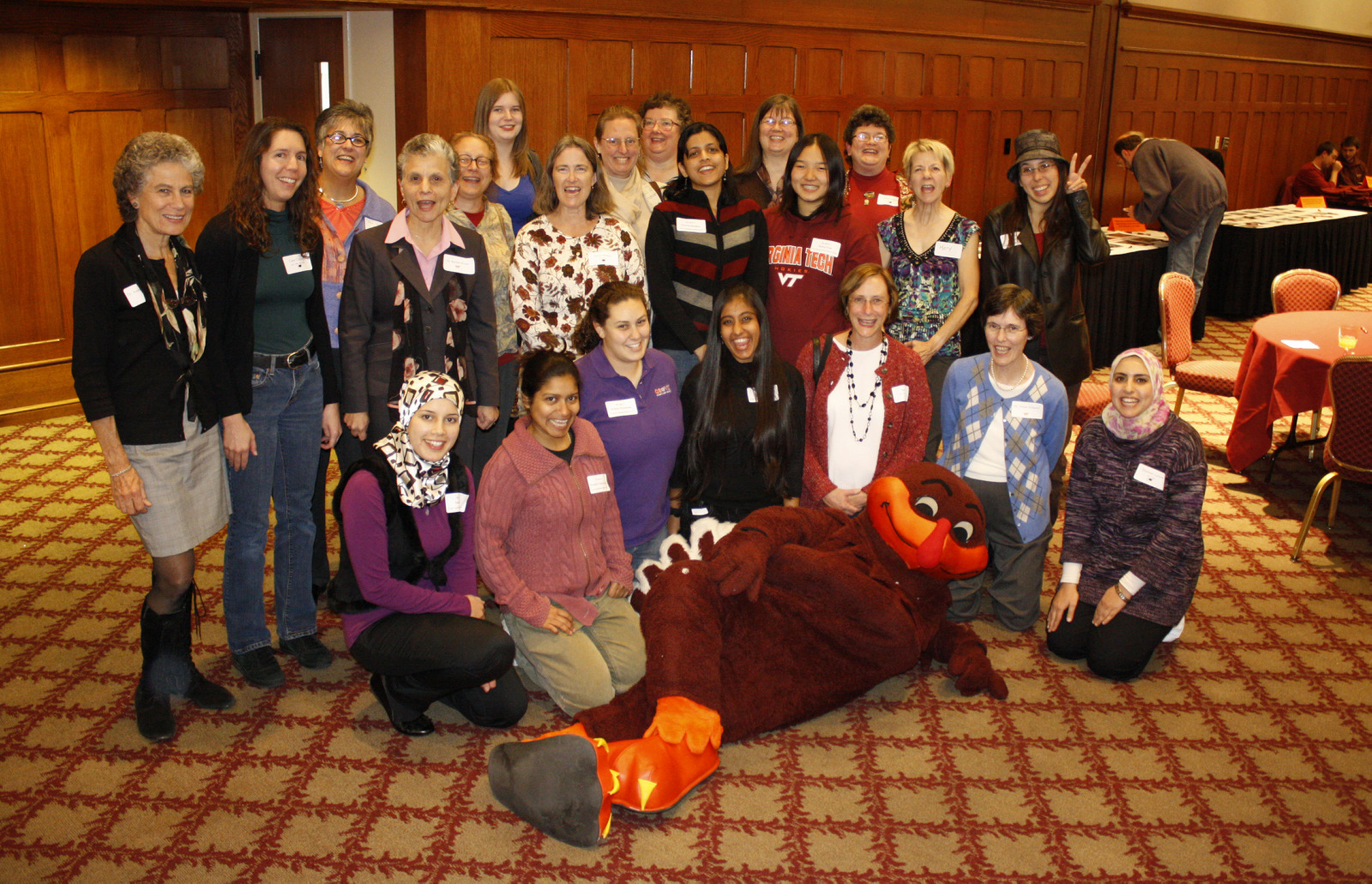 Computer science female students and graduates with Hokie bird