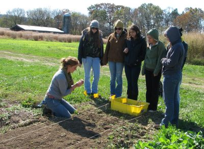 Chelsea Graves teaches student volunteers how to plant garlic.