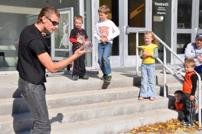 Youngsters watch with anticipation as a Virginia Tech student entertains them with illusions.