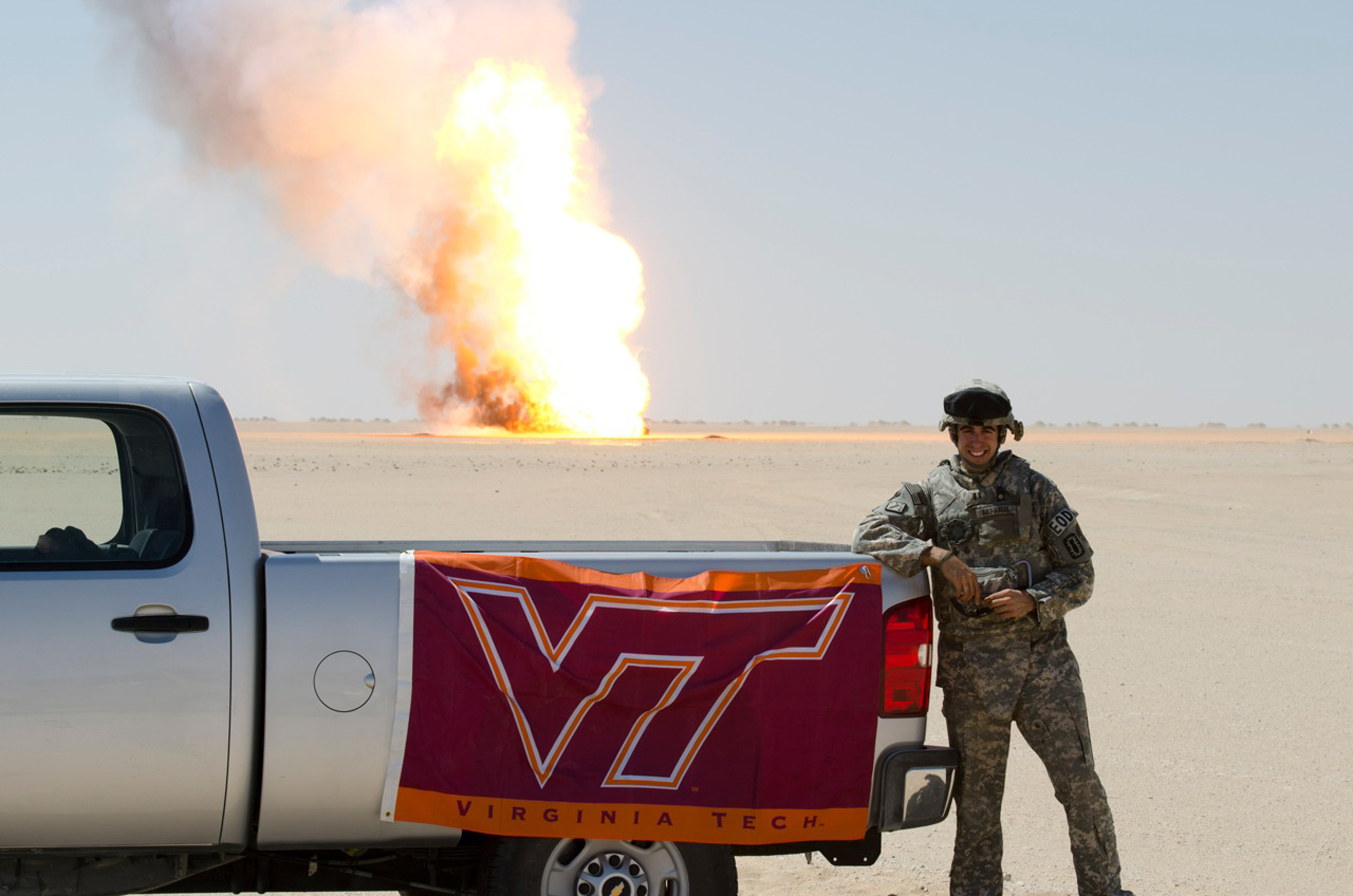 Capt. Amir Abu-Akeel, U.S. Army, Virginia Tech Corps of Cadets Class of 2006 standing in front a controlled explosion from his deployed location