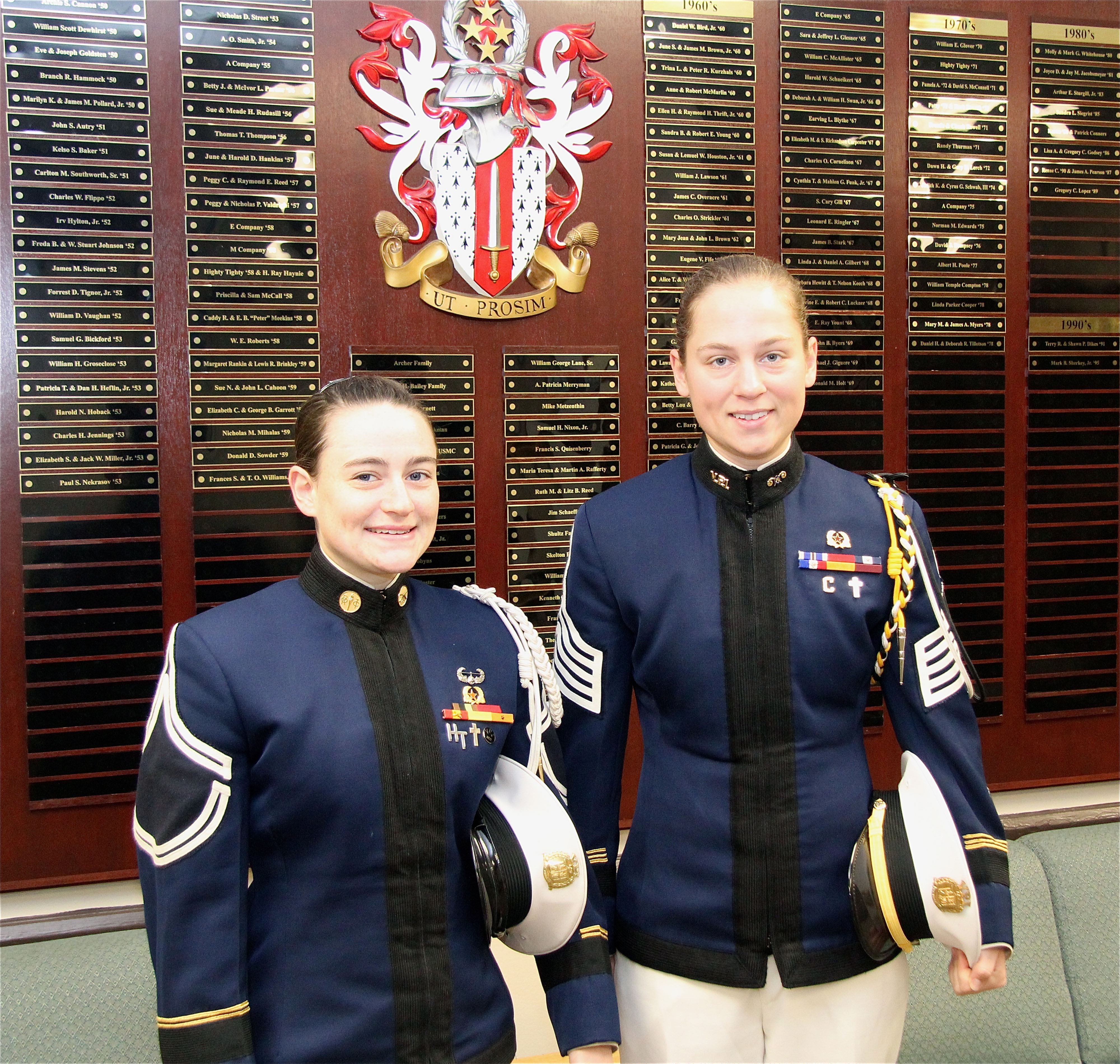 From left to right are Cadets Elaine Altman and Faith Mueller in front of the Corps of Cadets Donor Wall