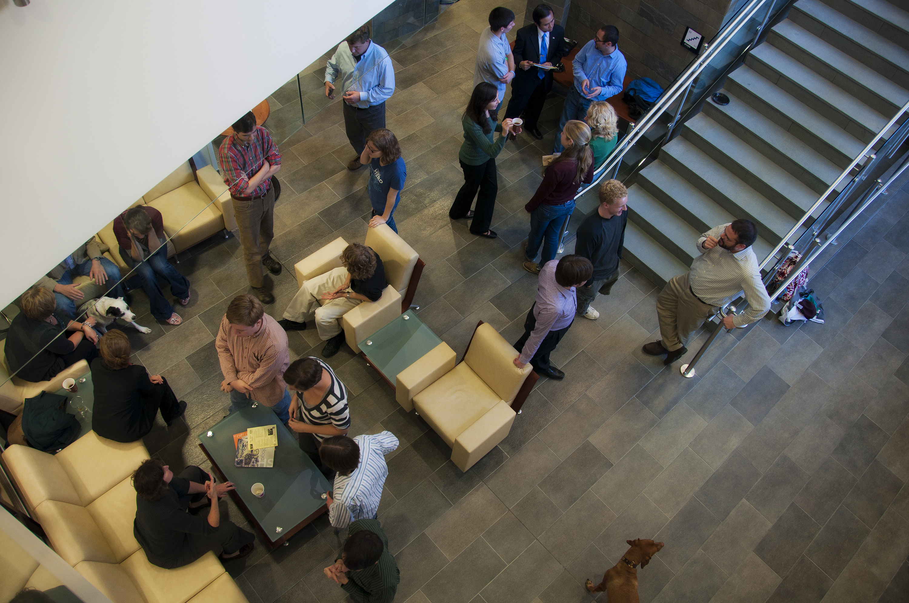 View looking down on a large group of students, faculty, and staff interacting in an open atrium area.
