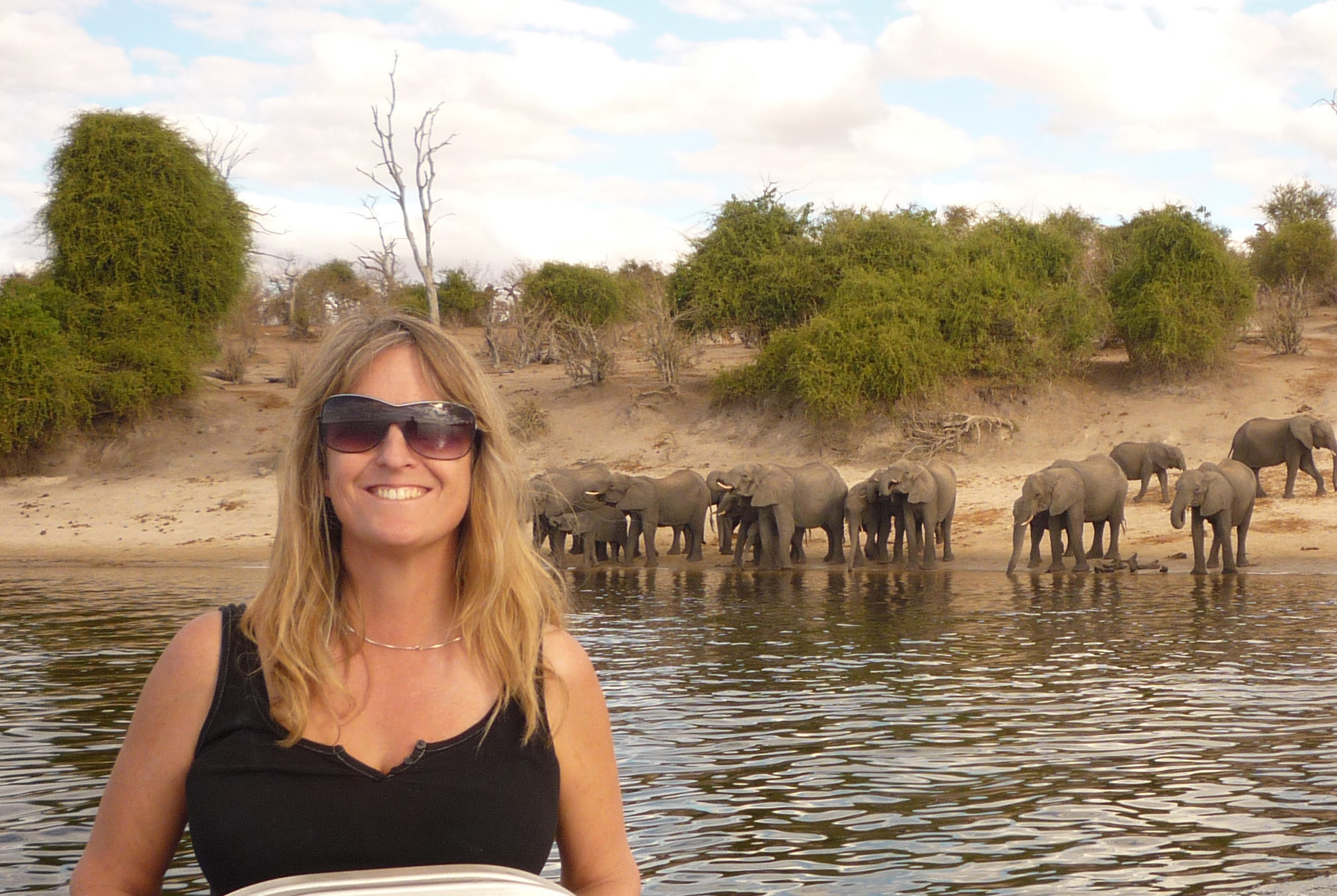 Kathleen Alexander at the helm of a small boat with elephants standing on the shore in the background