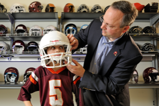 Stefan Duma, head of the Virginia Tech -- Wake Forest School of Biomedical Engineering and Sciences, fits a football helmet on his son, Brock, age 8. Youth football players Brock's age wear the same size helmets as adult players, but with more padding to fit.