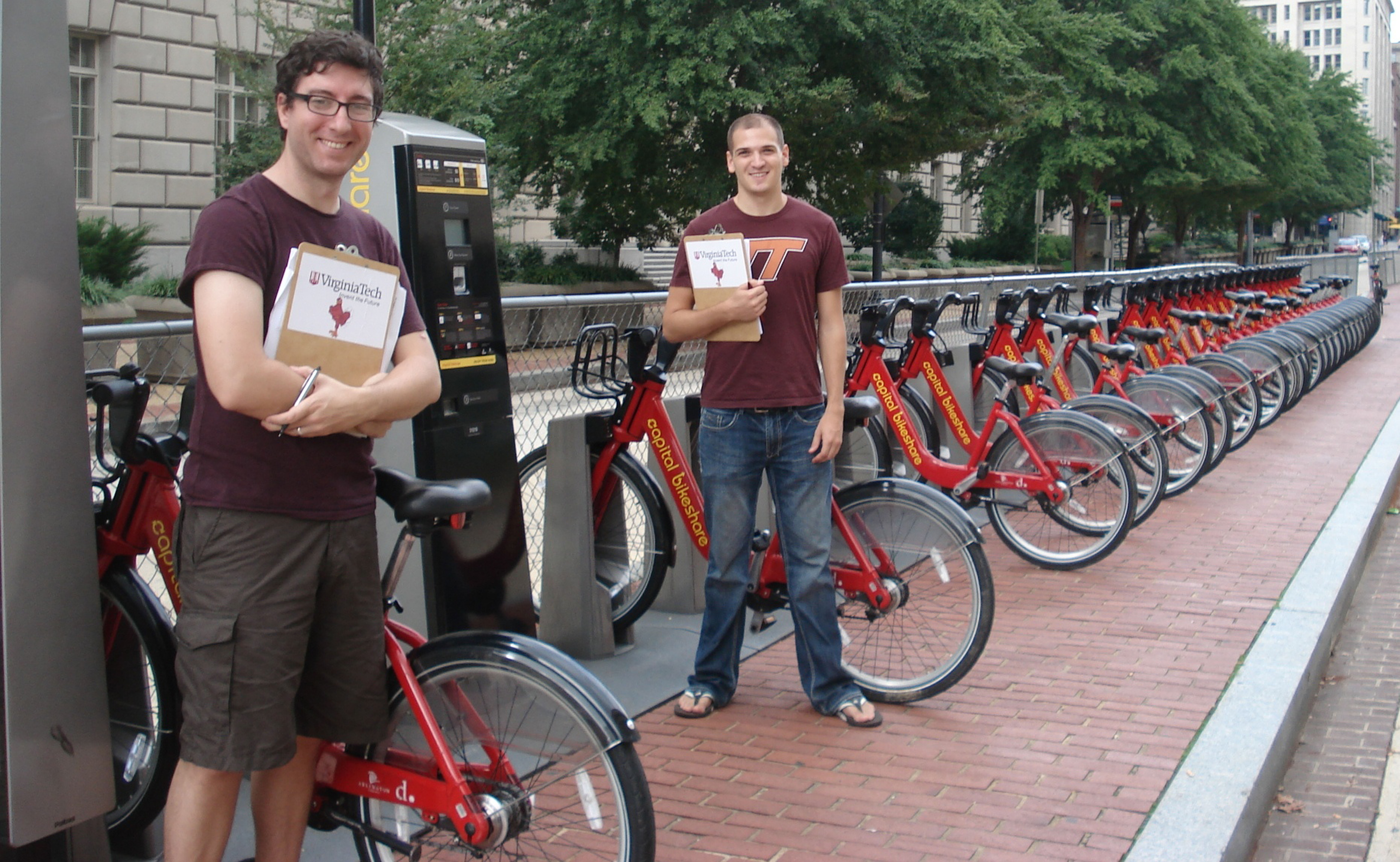 Tim Maher (left) and Austin Watkins (right) stand ready to take surveys at Capital Bikeshare station