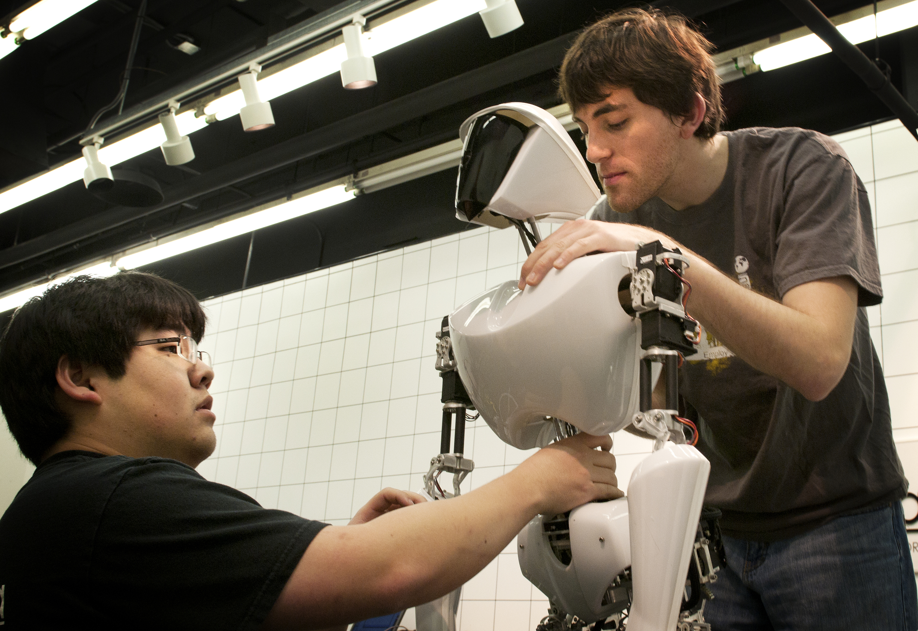 (Left to right) Mechanical engineering doctoral student Bryce Lee and mechanical engineering master's student Coleman Knabe work on CHARLI 2, a soccer-playing humanoid robot built in the Robotics and Mechanisms Laboratory, part of the College of Engineering.