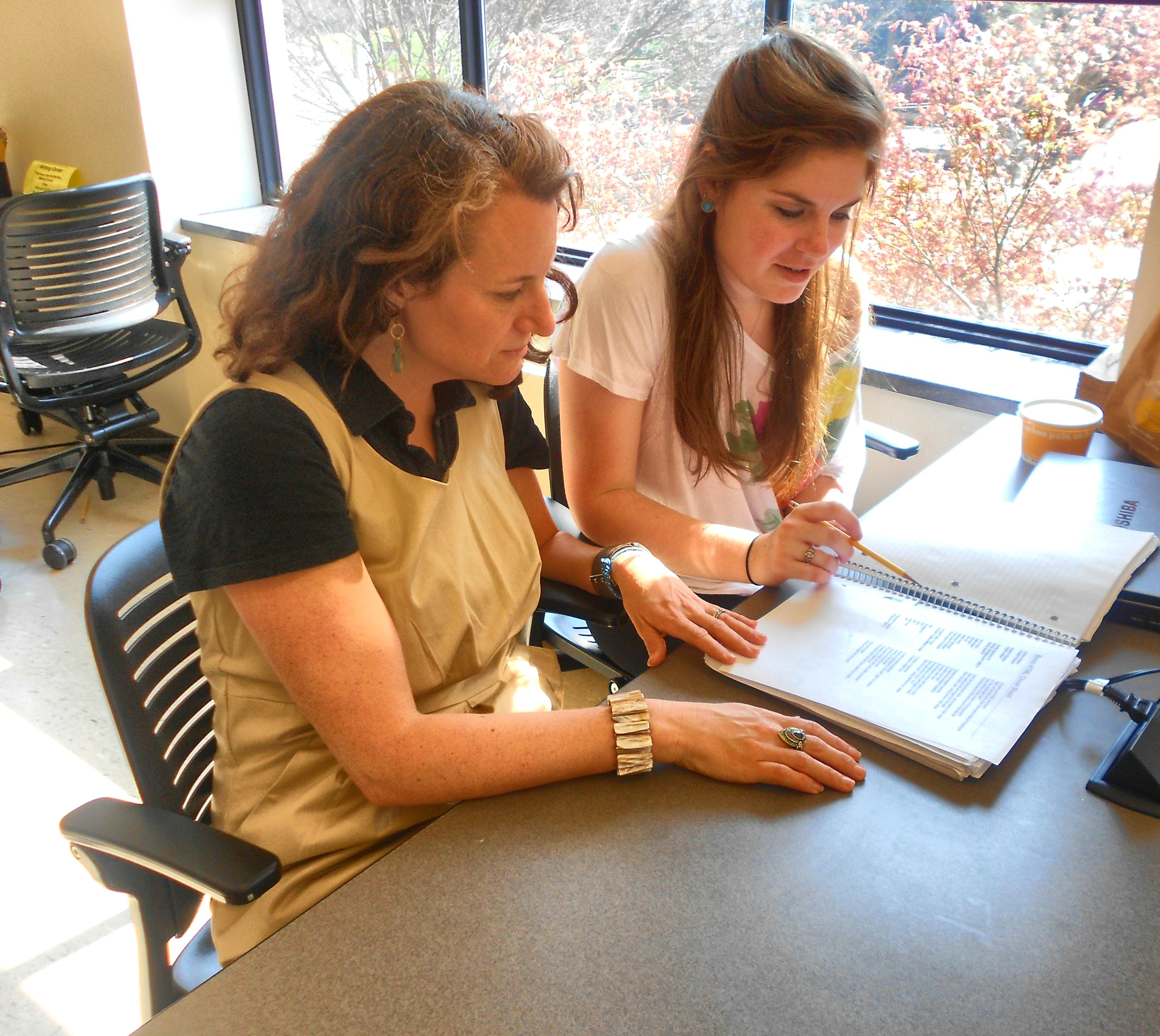 Director and student collaborating on paper