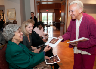 "World renowned Virginia Tech poet Nikki Giovanni presents Esther Jones, lifetime resident of Wake Forest, with a copy of the illustrated poem, ""These Women."" Morgan Cain Grim, the 2009 Steger Poetry Prize award winner looks on along with Benzena Eaves, another community member of Wake Forest."