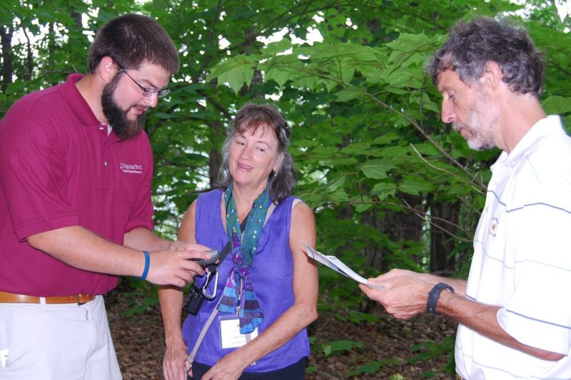 An instructor showing two participants how to use a GPS in a wooded setting.