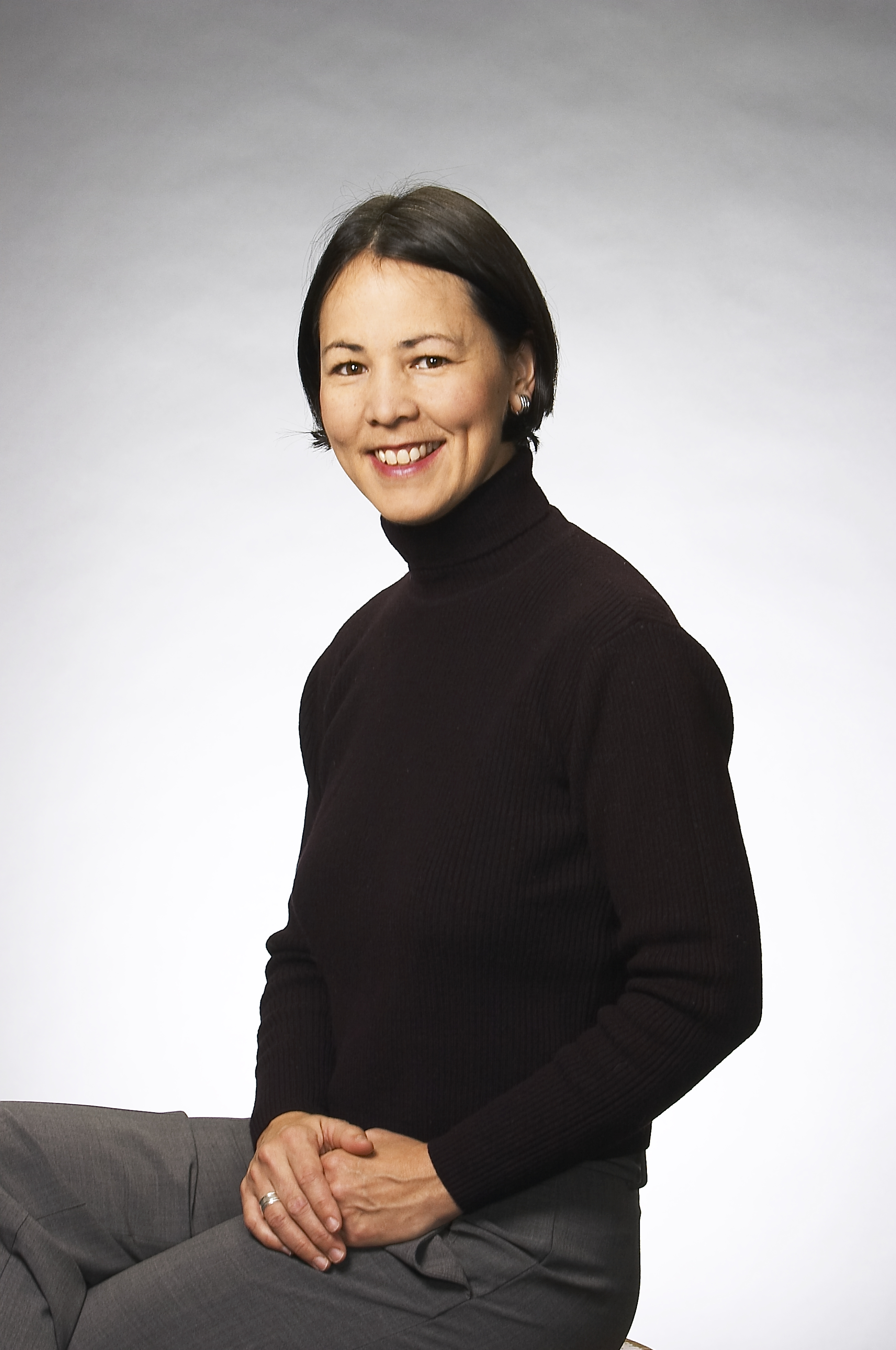 Radio announcer May-Lily Lee sitting on a stool in a pose. She is wearing a long-sleeved black turtle neck and gray pants. She is smiling and her hands are resting one atop the other on her leg.