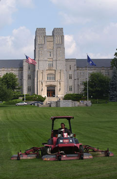 An employee mows the lawn in front of Burruss Hall.