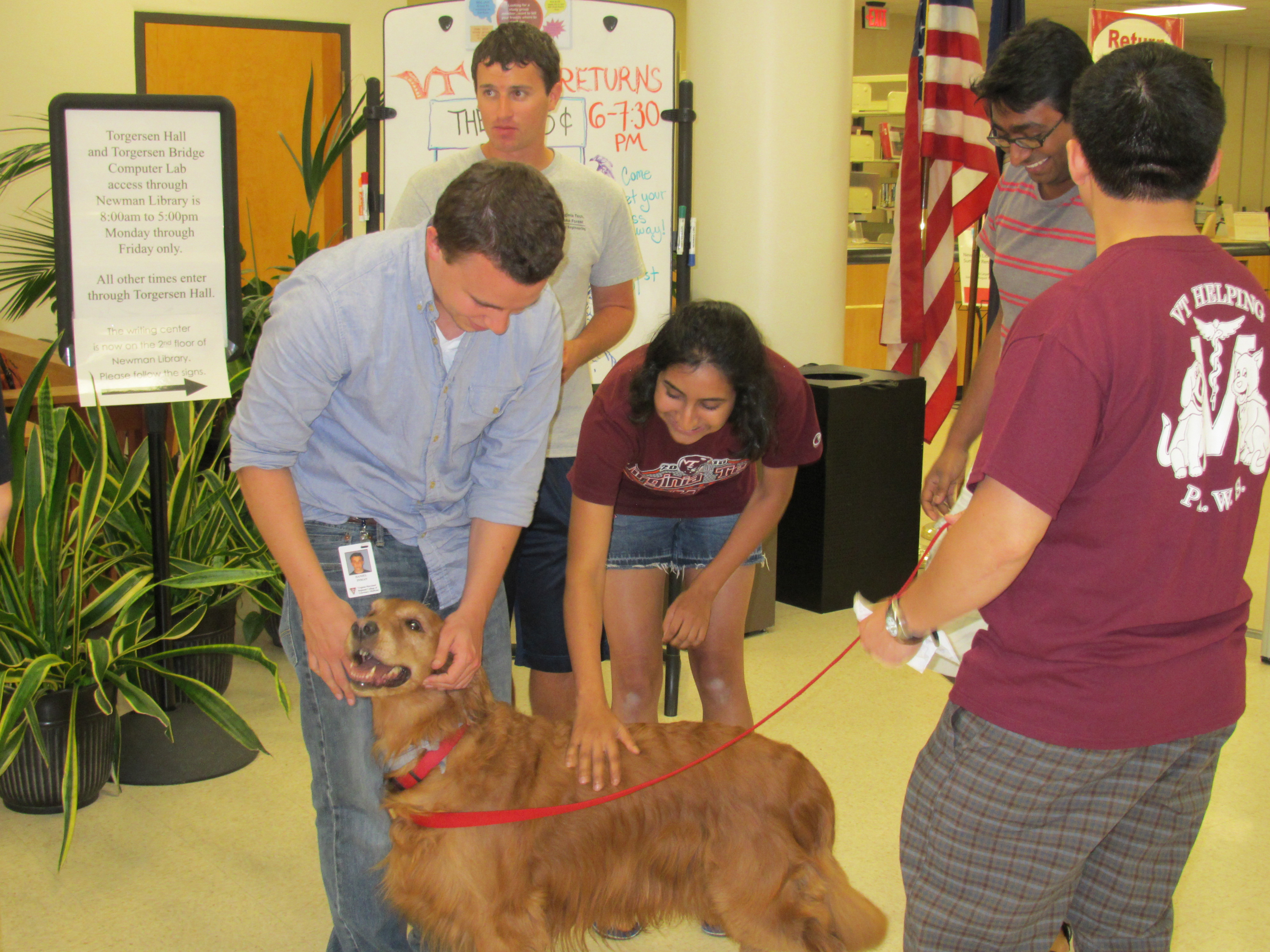 Virginia Tech students pet therapy dogs at the library.