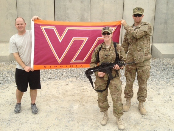 Standing in front of the VT flag is Capt. Kim French, U.S. Air Force, Virginia Tech Corps of Cadets Class of 2005 while on deployment in Afghanistan