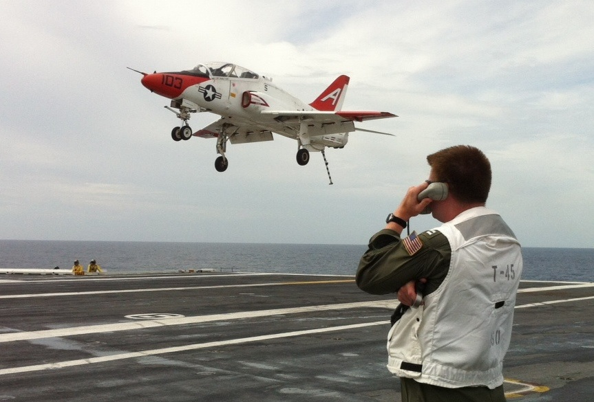 A Boeing T-45C Goshawk flies during a carrier landing with Lt. Michael Renard, U.S. Navy, Virginia Tech Corps of Cadets Class of 2004 in the foreground.
