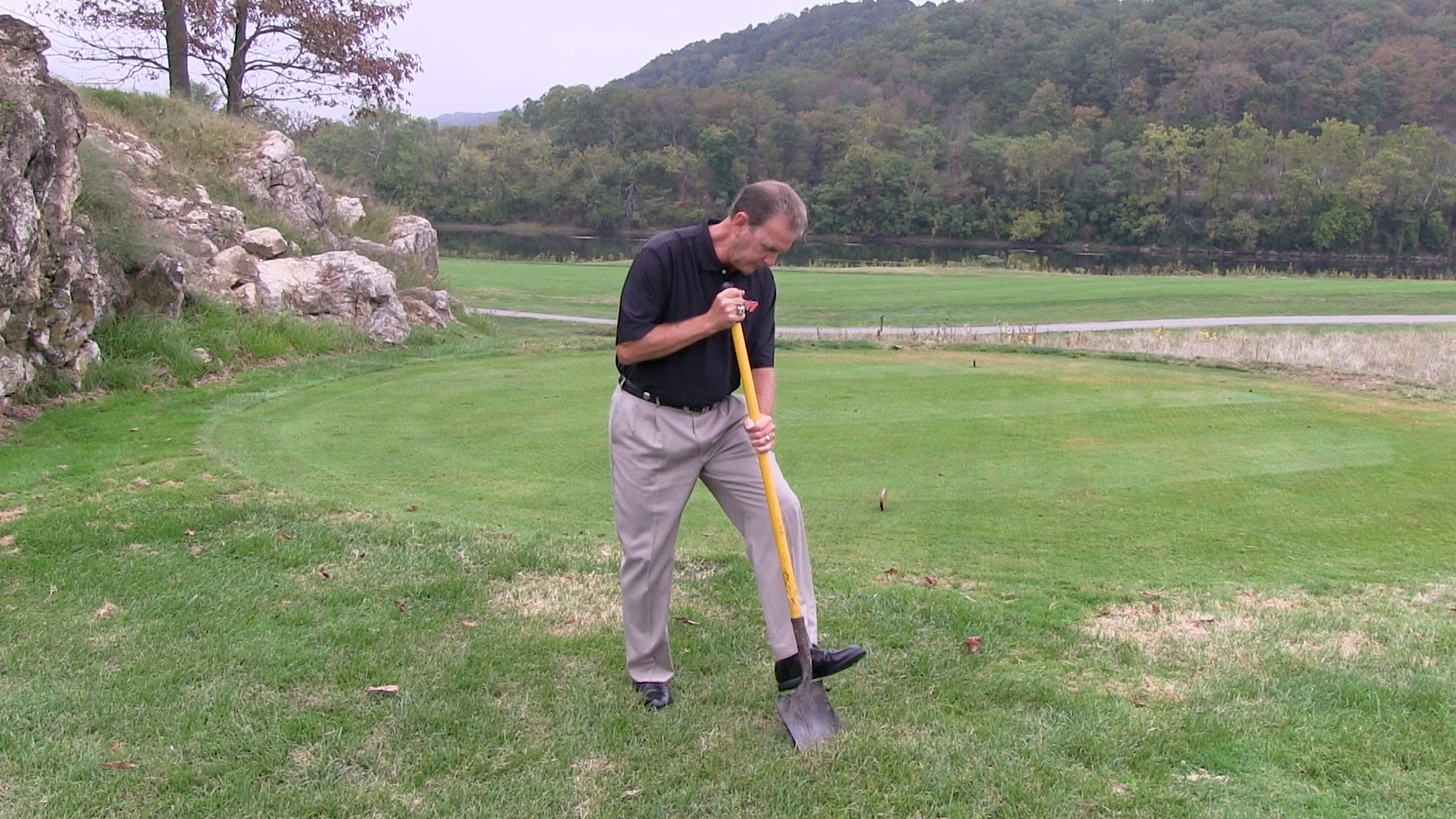 The head golf coach at Virginia Tech, Jay Hardwick, uses a shovel to dig up some soil. He's checking to see whether there are any layyers of clippings and dead roots.