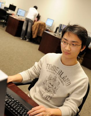 Graduate student at computer with other students in background.