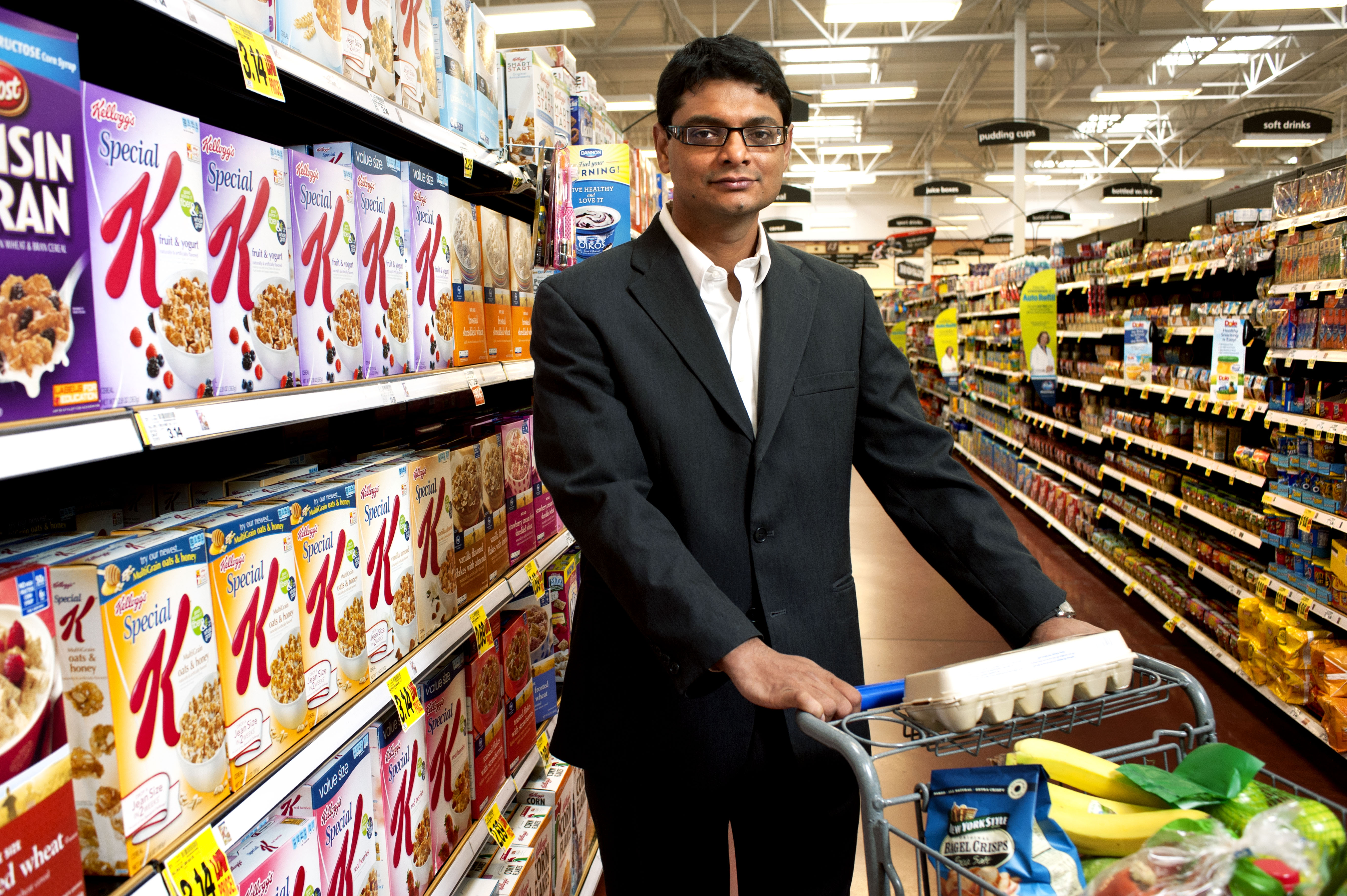 Marketing associate professor and consumer behavior researcher Rajesh Bagchi stands next to colorful boxes of cereal in a grocery store.