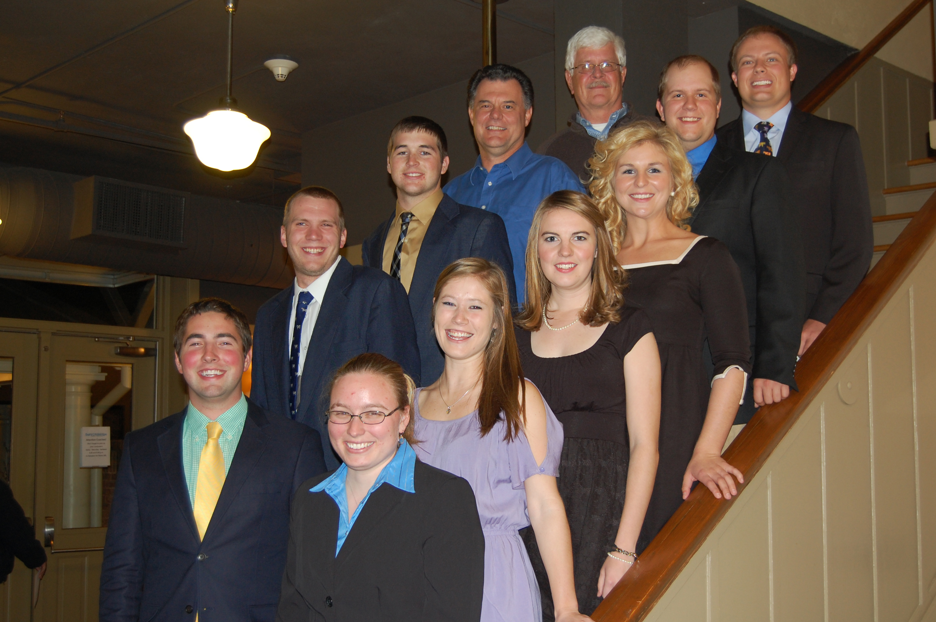 A group photo of nine students and two professors standing on a staircase. The students participated in the North American Intercollegiate Dairy Challenge.
