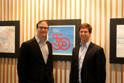 Rocco Piscatello and David Spradlin stand in front of a wall displaying a 50th anniversary icon design.
