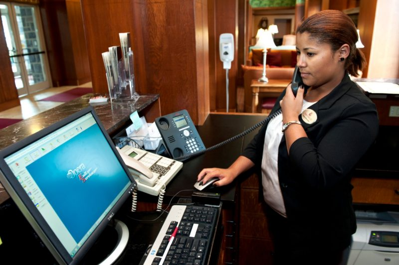 A hotel front desk clerk uses one of the new phones installed as part of the unified communications switchover