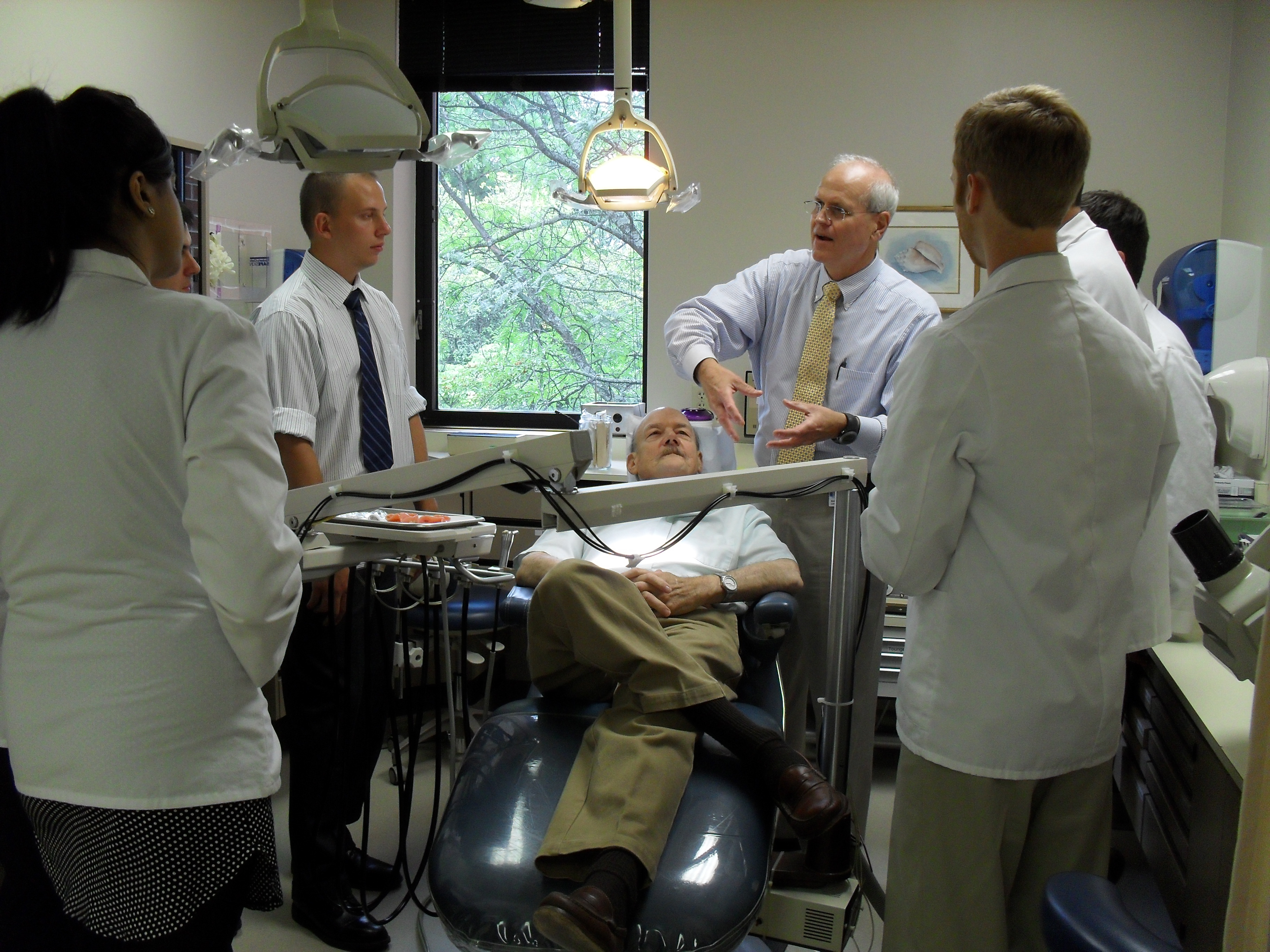 "Charles ""Bud"" Conklin, DDS, teaches VTC School of Medicine students how to perform an oral exam."